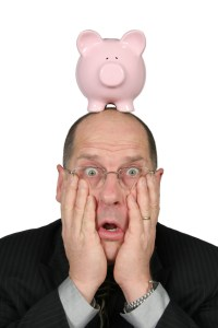 business man with piggy bank on head and hands on