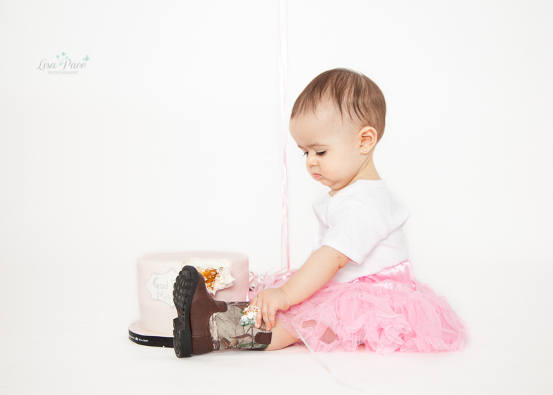 girl in tutu and cowboy boots in front of cake