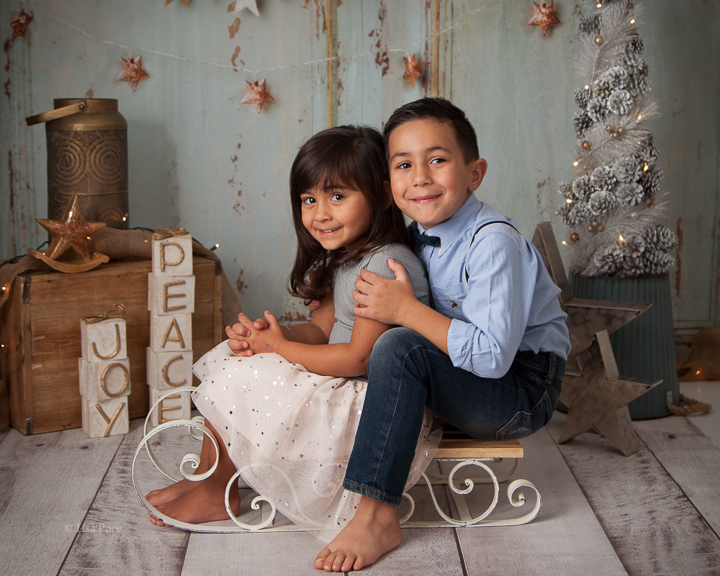 brother and sister sitting on sleigh