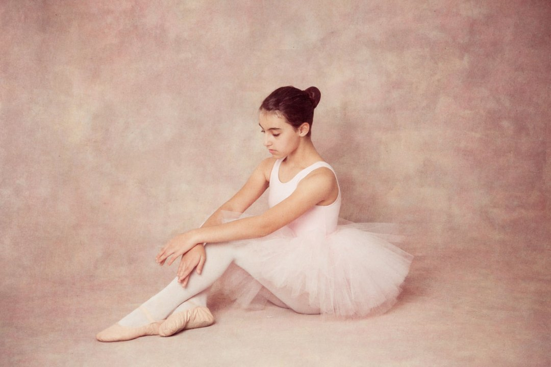 girl in ballerina tutu sitting and looking down