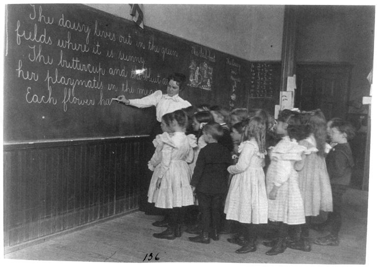 Elementary school children standing and watching teacher write at blackboard, Washington, D.C. c. 1899