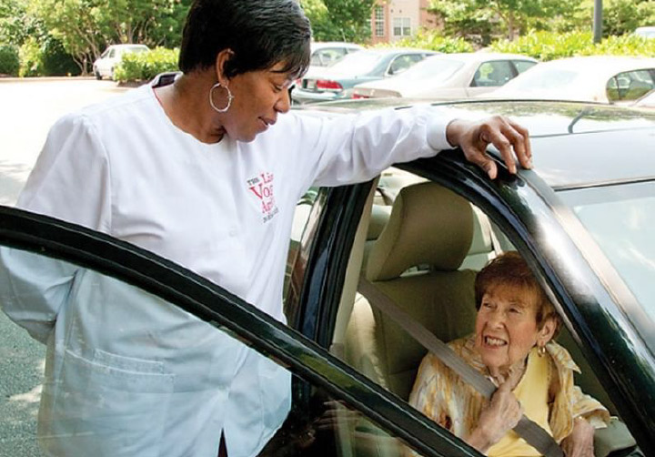 Image of Lisa Vogel employee helping a client from her car