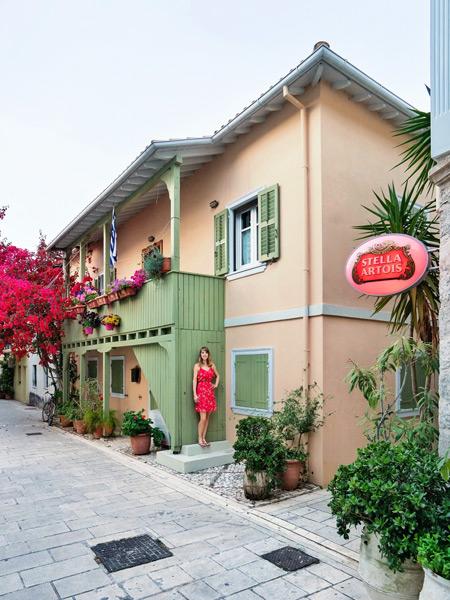 Vrouw in rode jurk bij gekleurd huis in Lefkas-Stad