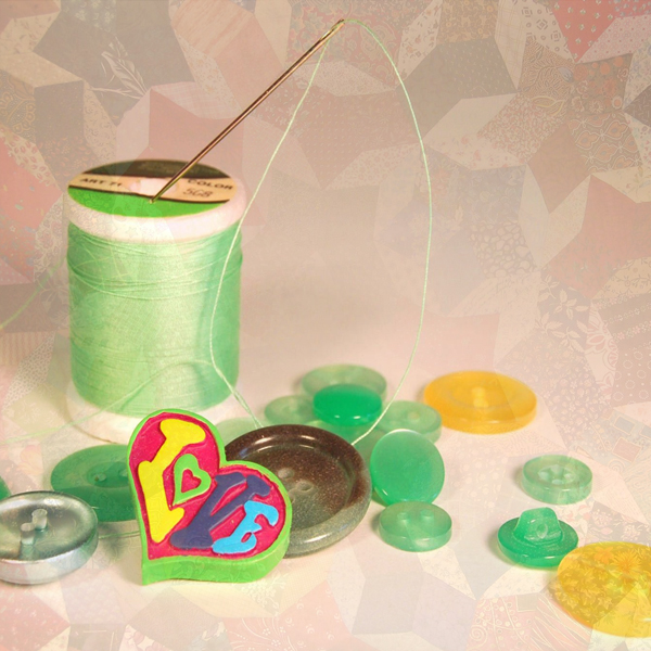 A need, thread, and buttons sit on top of a quilt. (Photo © FreeImages/Julia Freeman-Woolpert and Brano Hudak)