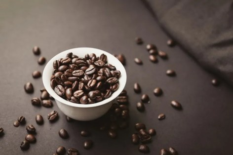 white bowl filled with coffee beans and coffee beans scattered
