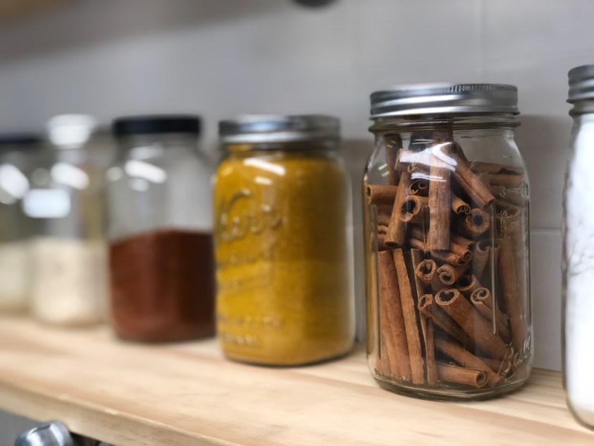 Spices on open shelves in minimalist kitchen.