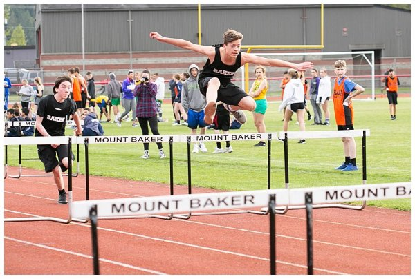 Tucker flying over the hurdles in track.