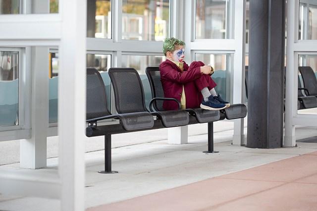 boy in bus station dressed in joker-inspired costume