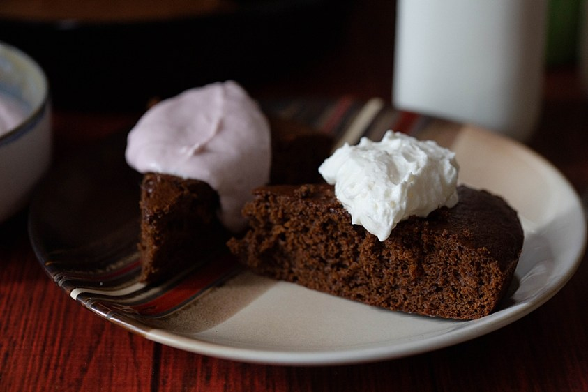 Homemade gingerbread served with a generous dollop of whipped cream.