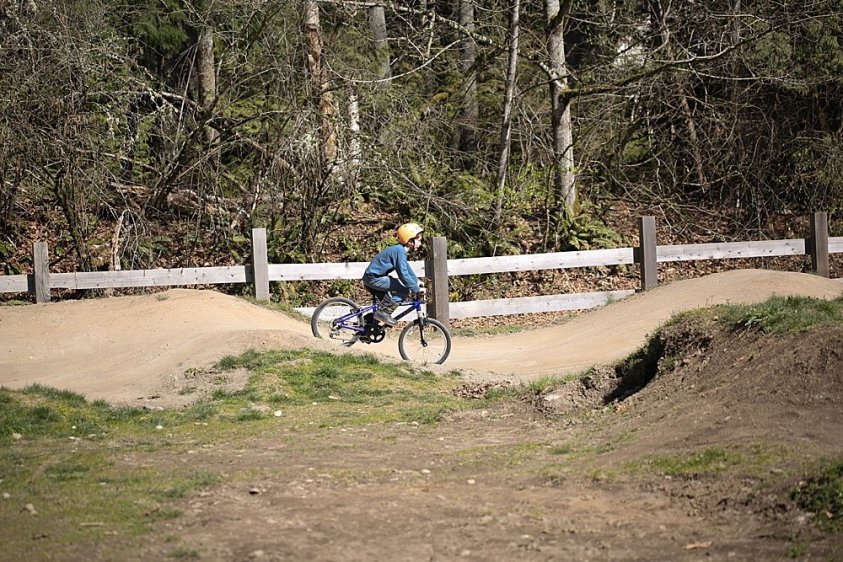 Apollo riding his bike on the bike track at Whatcom Falls.