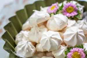Green bowl filled with crunchy and chewy meringues with pink flowers