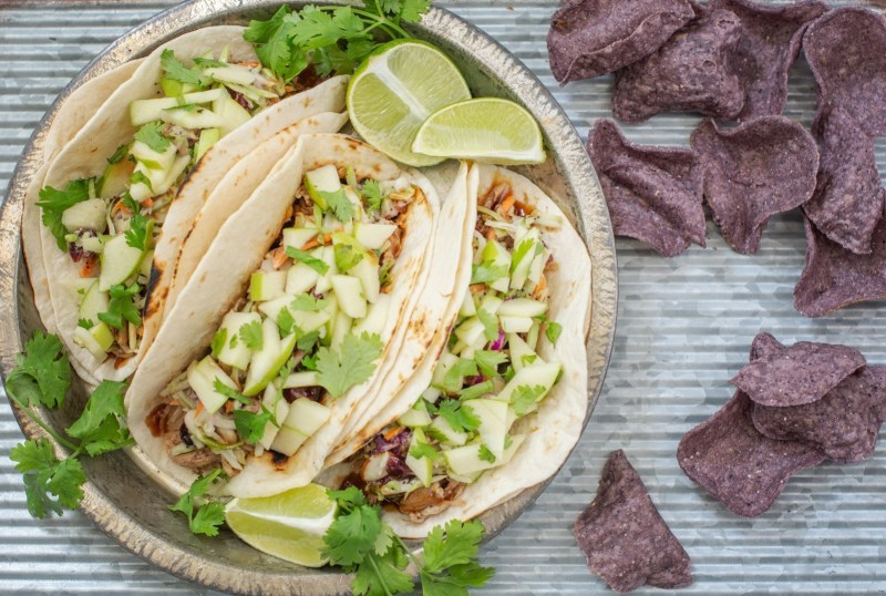 A plate of BBQ pulled pork tacos and a side of blue corn tortilla chips