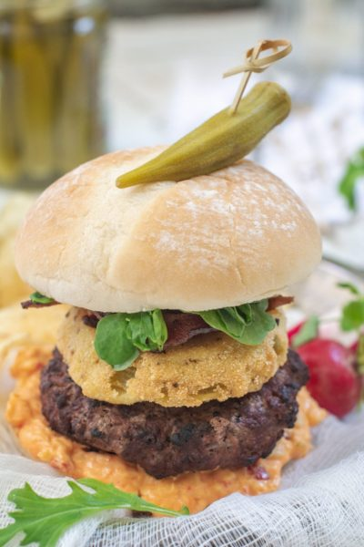 A Southern Burger topped with pimiento cheese, fried green tomatoes, lettuce and bacon.