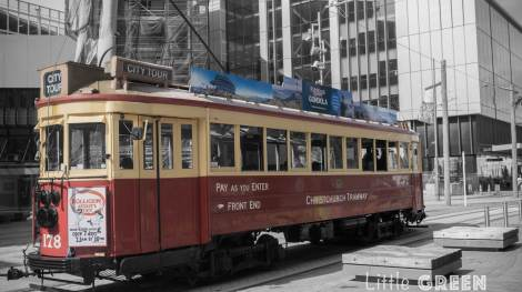 A vintage red tram takes tourists through the streets of Christchurch.