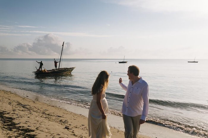 Pregnant bride and groom wave to fishermen on Guludo Beach in Mozambique. They were travelling abroad during pregnancy for a wedding.