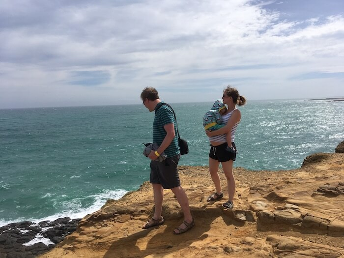 The author is carrying her eldest child on top of her pregnant bump as she and her husband walk along a cliff. They are travelling during pregnancy in New Zealand.