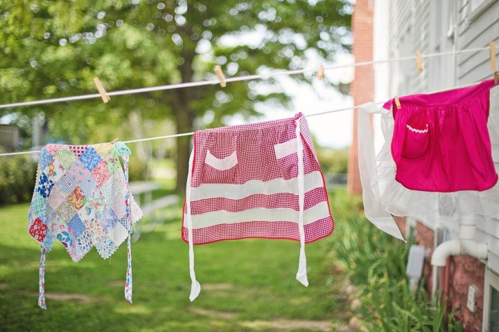 3 Vintage aprons, hanging on an outdoor clothesline.