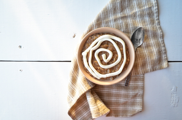 A warm, comforting bowl of cinnamon roll oatmeal, complete with a cream cheese swirl.