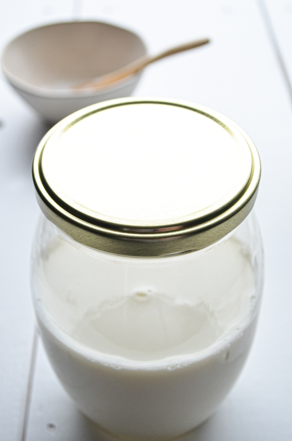 A jar, filled half way with milk, ready to become milk kefir.