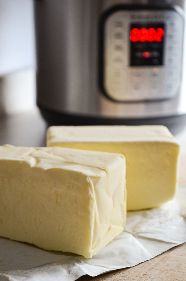 Two pounds of butter, laying on their wrapper, with an Instant Pot in the background.