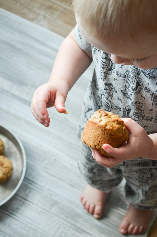 A toddler holding a sourdough discard muffin.