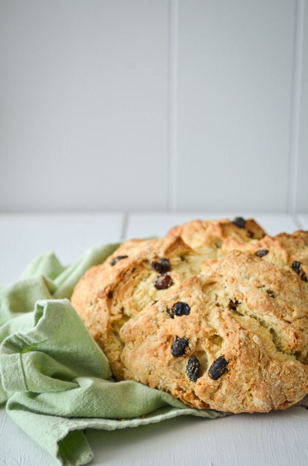 A loaf of sourdough discard Irish Soda bread, speckled with raisins and resting on a green cloth napkin.
