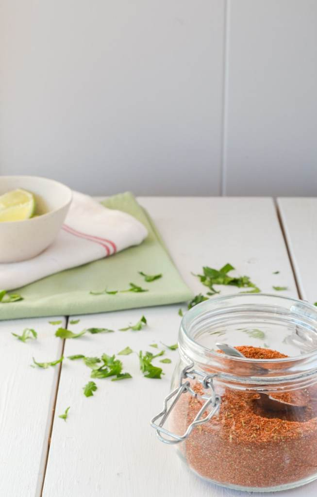 A white table with a jar of a spice mixture, cilantro sprinkled in the background, and two cloth napkins with a bowl of lie wedges.