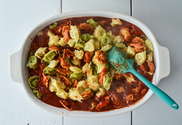 A baking dish is filled with tortellini and pasta sauce.