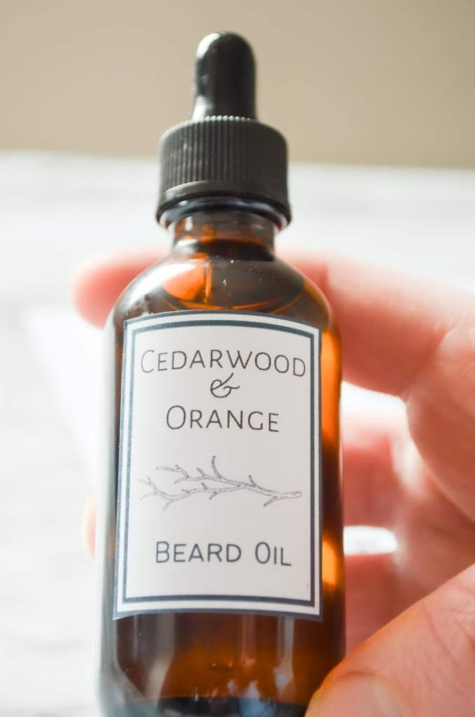 A bottle of Cedarwood and Orange Beard Oil being held by a close up hand.