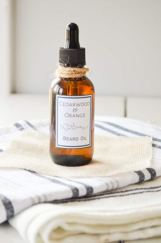 A bottle of fathers day beard oil, resting on several cloth napkins.