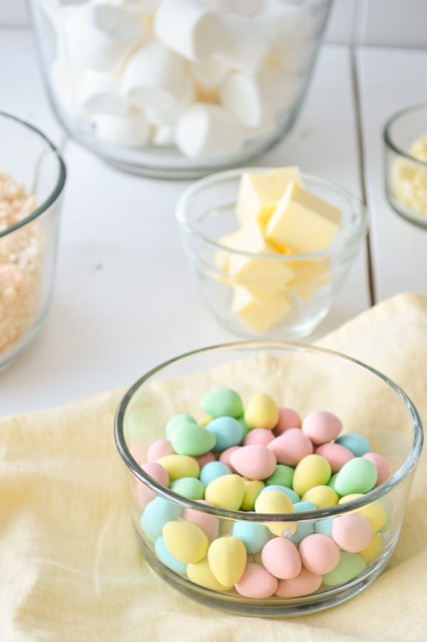 A glass bowl of mini eggs in the bottom right corner. A bowl of cubed butter, rice krispies, and marshmallows can be seen in the background.