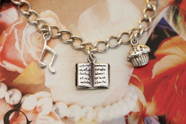 Silver Charm Bracelet: close up of quaver, musical note, book and cupcake