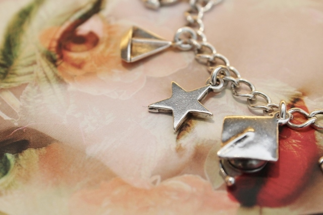 Silver Charm Bracelet: close up of Boat, Star and Graduation Cap