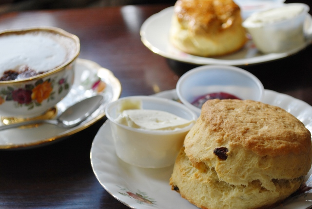 Fruit scones with jam and cream, cappuccino