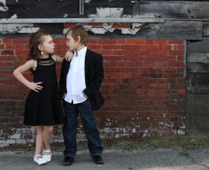 Portland Maine Portrait Photographer, boy in white dress up shirt and black blazer, levi jeans, girl in short black dress and white dress shoes standing in front of a brick wall