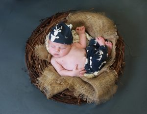 newborn baby curled up in brown nest, burlap, navy blue deer pants and hat