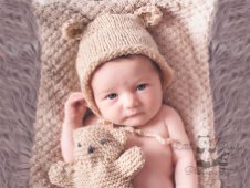 Baby girl awake in teddy hat