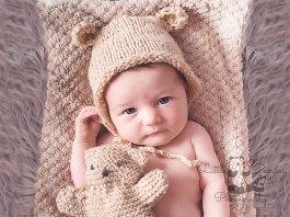 Baby girl awake in teddy hat
