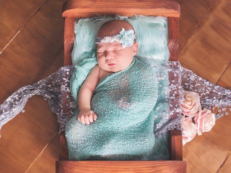 Baby girl in wooden bed