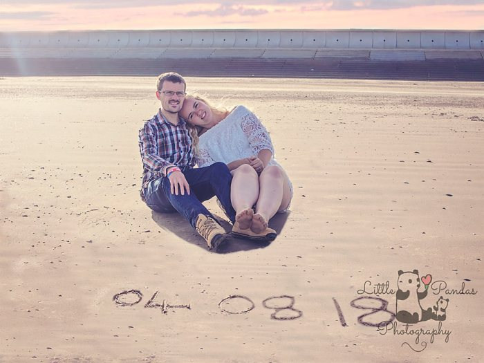 Engagement couple with wedding date in sand