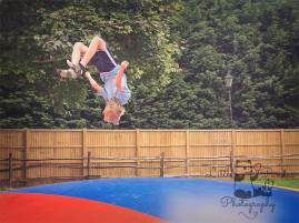 Boy doing backflips on bouncy castle
