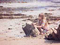 Little girl building sandcastle