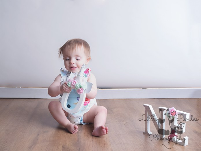 Little girl looking up pre cake smash