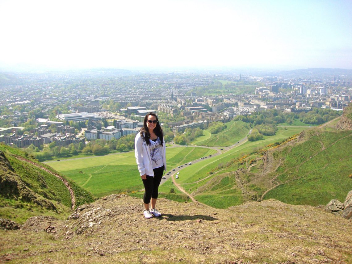 Woman in white shirt and black leggings wearing sunglasses standing on hill outside with view of green grass and Edinburgh, Scotland cityscape behind her