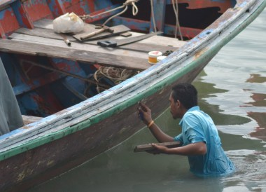 Local in Water Fixing Boat, Village Coconut Island Resort Phuket Hotel