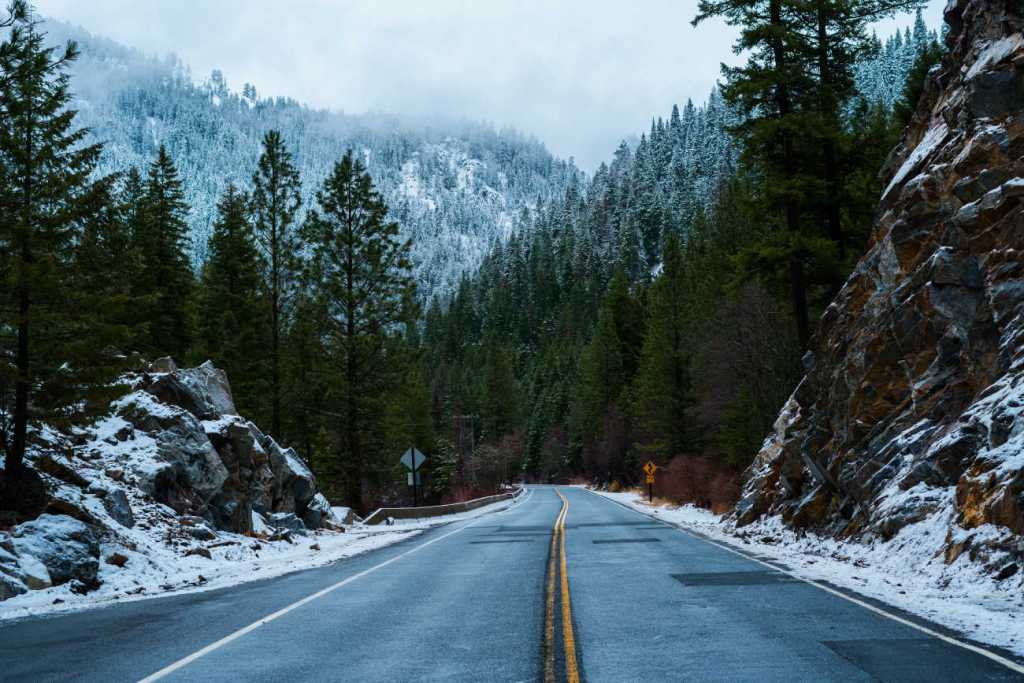 Empty two lane road in snowy forest