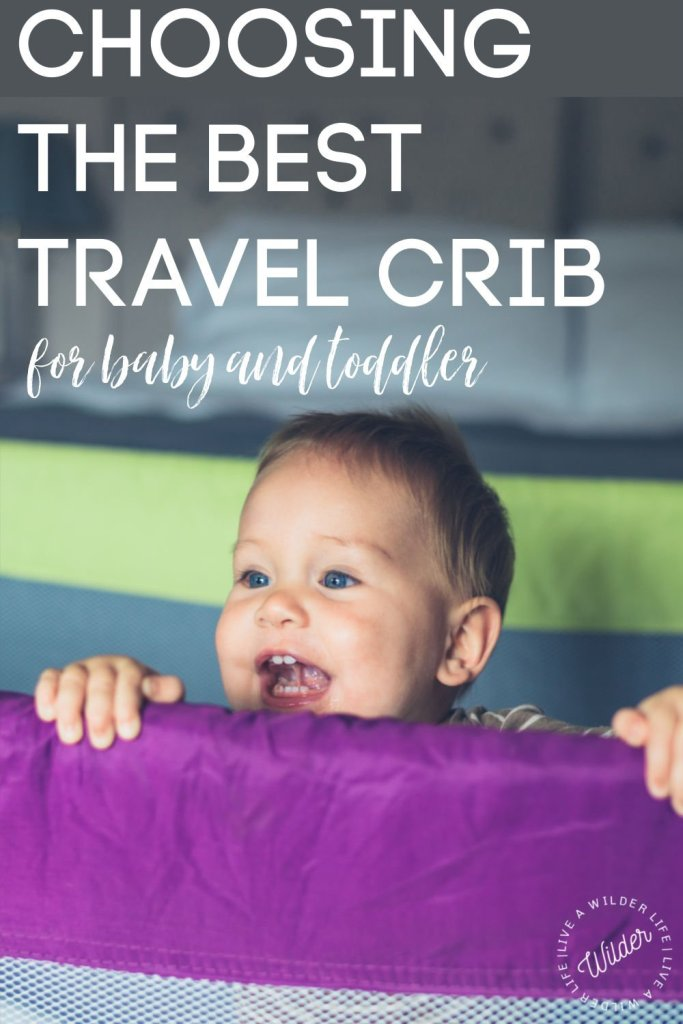 baby peering over portable travel bed