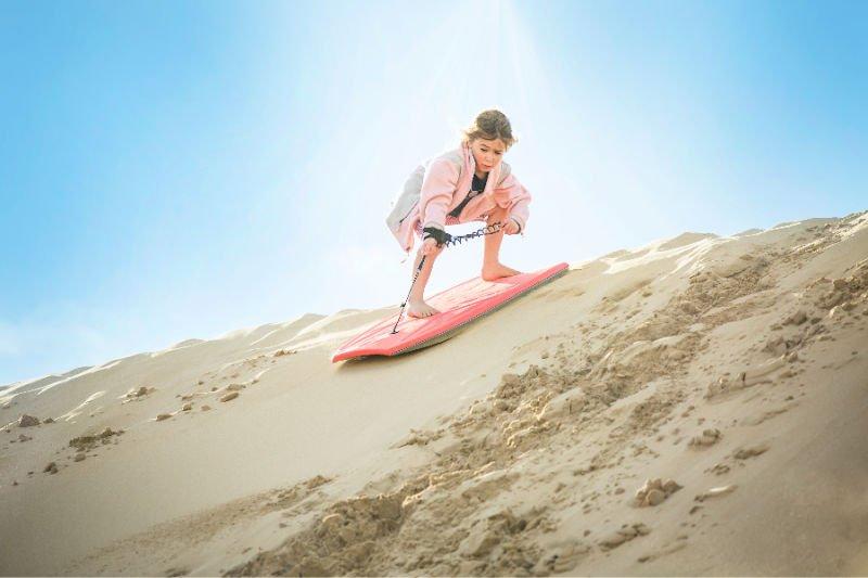 girl sand surfing down sand dune