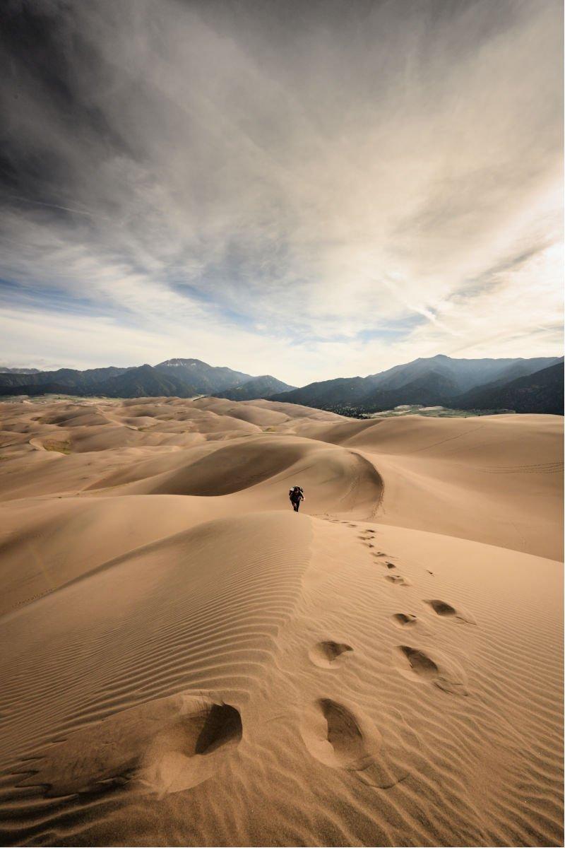 figure walking on tall sand dunes