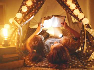 mom and children reading books in a tent